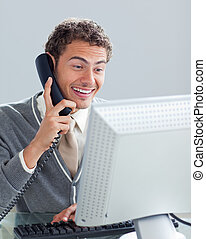 Charming businessman on phone at his desk