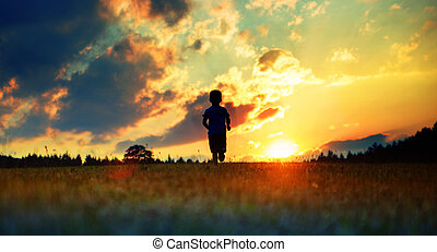 Cheerful boy running towards the sunset - Cheerful child...