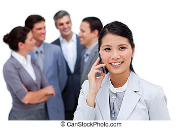 Jolly businesswoman talking on phone in front of her team