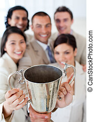 Successful business team showing their throphy in a company