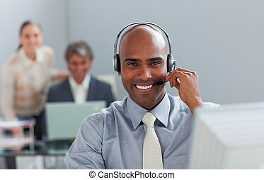 Afro-american  businessman with headset on working at a computer in the office