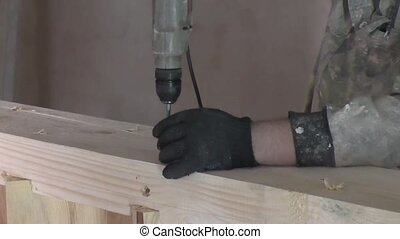 Man turns the screw a Board drill , manufacture of wooden...