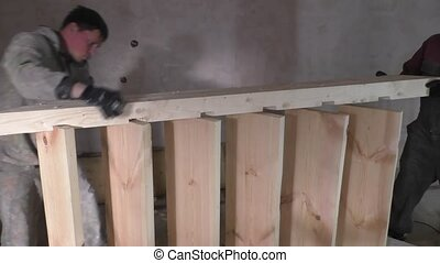 Two workers make wooden staircase, carpentry