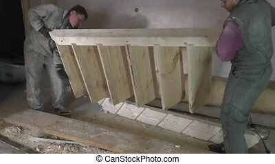 workers rearrange wooden staircase - Two workers rearrange...