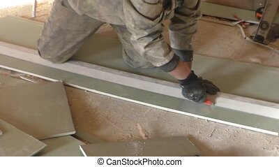 A worker cuts a plaster sheet knife
