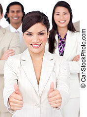 Attractive businesswoman and her team with thumbs up against...