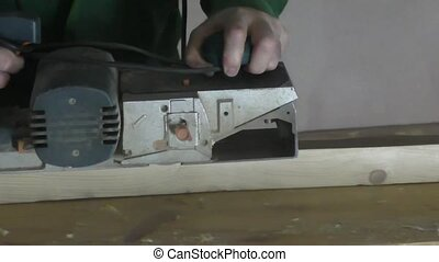A man working mustard electric is a wooden block