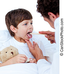 Male doctor checking little boy\'s throat in a hospital