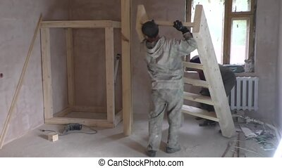 Two workers install staircase - Two workers install wooden...