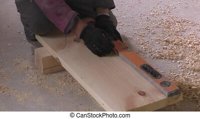 Man measures the wooden board, 