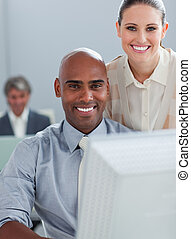 Radiant businesswoman helping her colleague at a computer in...