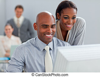 Smiling business partners working at a computer together in...