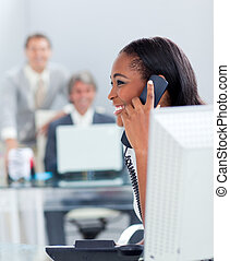 Smiling businesswoman on phone at her desk