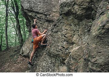 Man bouldering on stone rock - Free climber man starting to...
