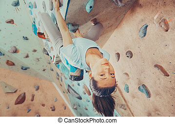 Smiling young woman climbing indoor - Smiling young woman...