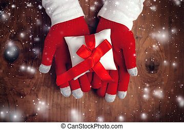 Present on Christmas eve, woman offering wrapped gift in...