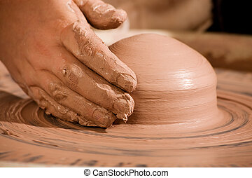 Hand shaping wedge of clay on spinning potters wheel