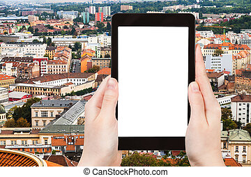 tourist photographs Brno city skyline on tablet - travel...