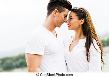 Young beautiful couple rubbing noses as a sign of love and...