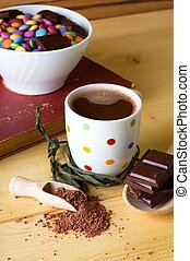 Table with hot chocolate and bowl with sweets - Vertical...