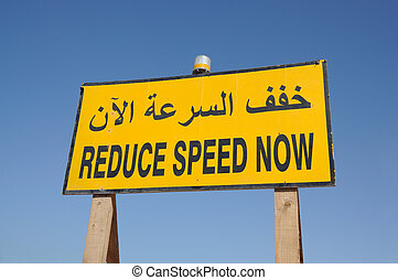 Reduce Speed Now sign in english and arabic language Dubai,...