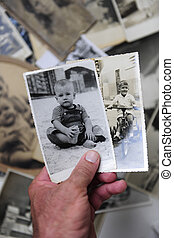 childhood: man holding photo of himself as a boy -...