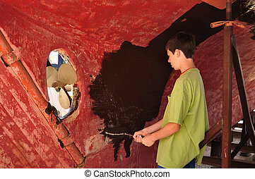 Teen Boy Painting Sailboat Hull with a Roller, copy space