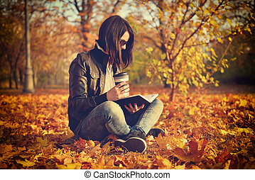 girl with coffee cup reading a book, sitting on leaves....