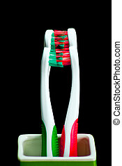 toothbrushes - red and green toothbrushes on black...