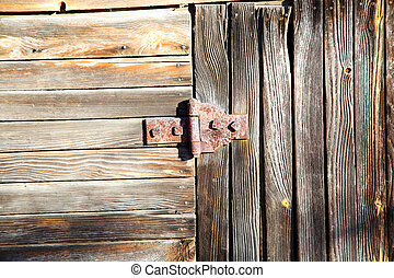 old rusty door hinge on old wooden door