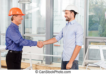 Cheerful male engineers made the deal with handshake -...