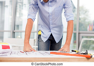 Cheerful male architect is working at the office - Close up...