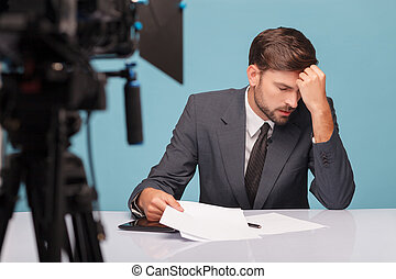 Handsome male newscaster is suffering from headache -...