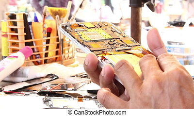 Technicians are repairing phone - Technicians are repairing...