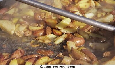 Fried potato in a cauldron - The person cooks potato in hot...