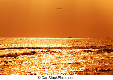 plane flies against the backdrop of the setting sun and the...
