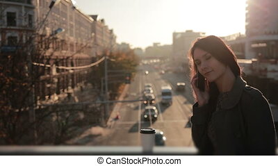 pretty woman talking on the phone on a city bridge - young...