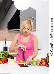 woman using a tablet computer to cook - Blonde woman using a...