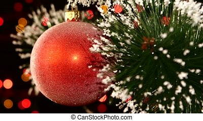 Unusual decoration - a round shiny red toy on christmas tree, bokeh, light, black, garland, cam moves to the left