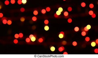 Unusual decoration - a round shiny red toy on christmas tree, bokeh, light, black, garland, cam moves to the right