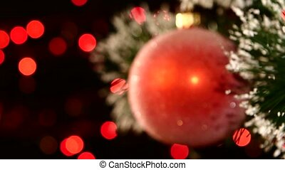 Unusual decoration - a round shiny red toy on christmas tree, bokeh, light, black, garland, dynamic change of focus