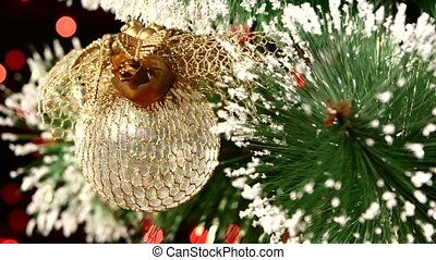 Unusual decoration - a round shiny gold toy on christmas tree, bokeh, light, black, garland, close up