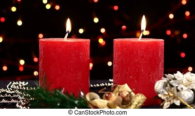 Two red candles with christmas decorations on black, bokeh, light, garland
