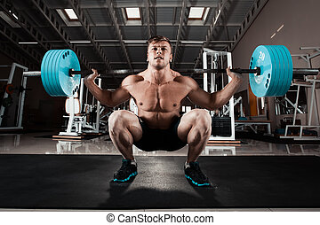 Man at the gym. Execute exercise squatting with weight, in...