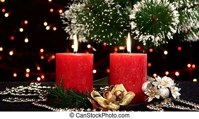 Two red candles with christmas decorations and tree on...