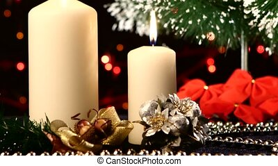 Two big white candles with christmas decorations like red bow, balls and tree on black, bokeh, light, garland, cam moves upwards
