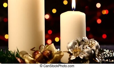 Two big white candles with christmas decorations like red bow, balls and tree on black, bokeh, light, garland, cam moves upwards, close up