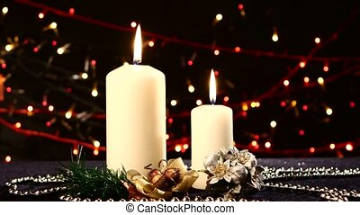 Two big white candles with christmas decorations on black,...