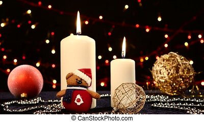 Two big white candles with balls and teddy for christmas on black, bokeh, light, garland