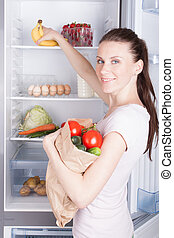 Woman near the refrigerator with healthy food.